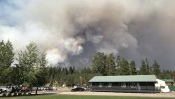 Smoke plumes rise from the Rice Ridge Fire in August, behind Montana's Seeley Lake Elementary School, in Seeley Lake, Mont.